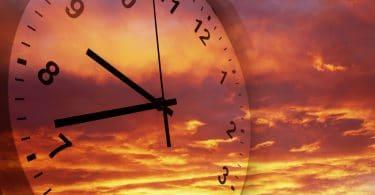 Imagem de relógio de parede com um pôr do sol avermelhado ao fundo.