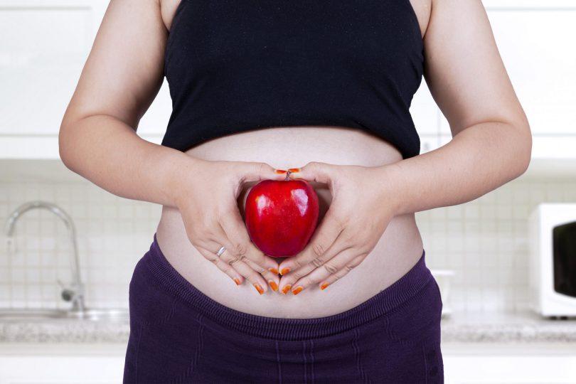 Mulher grávida segurando uma maça vermelha em frente da sua barriga.