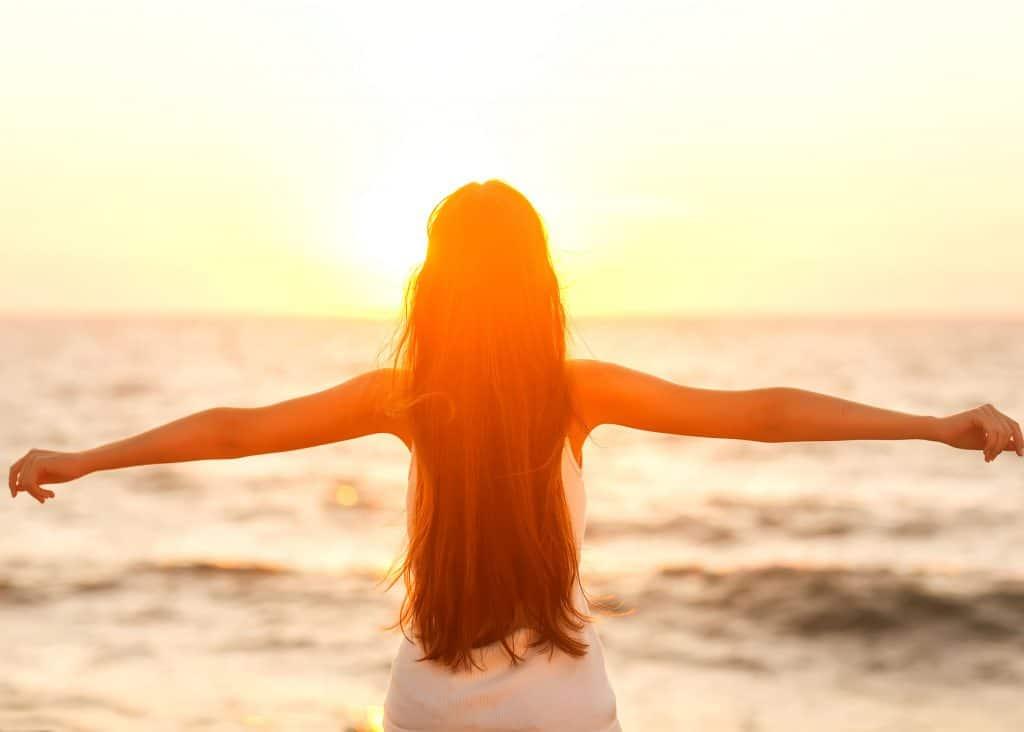 Mulher de costas com os braços abertos e ao fundo há a paisagem de uma praia ao fim de tarde.