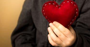 Mão de uma criança branca segurando um coração de pano vermelho.