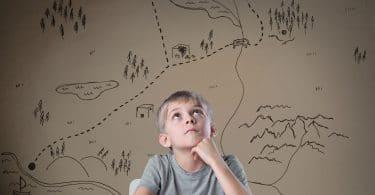 Menino branco e loiro, sentado em uma mesa, com um livro aberto, com vários desenhos de mapa ao seu fundo.