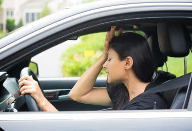 Mulher dentro do carro, vestida de preto , com a face preocupada e com a mão na cabeça.