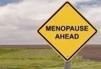 Placa de trânsito escrito: Menopausa à frente, em inglês.