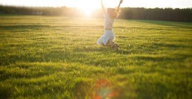 Mulher com os cabelos soltos, correndo em um campo verde, com os braços pra cima e luz do sol brilhando ao fundo.