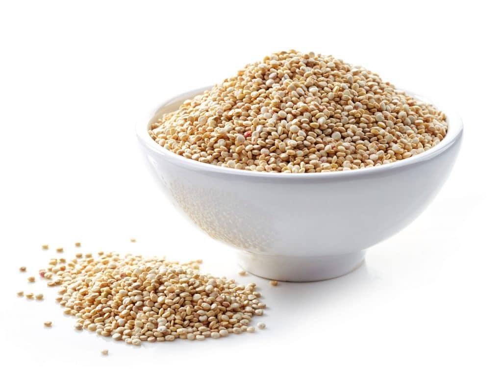 Uma vasilha branca com grãos de quinoa dentro.