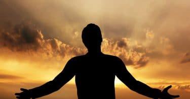 Silhueta de homem com os braços abertos em frente à um céu iluminado pelo pôr do sol.