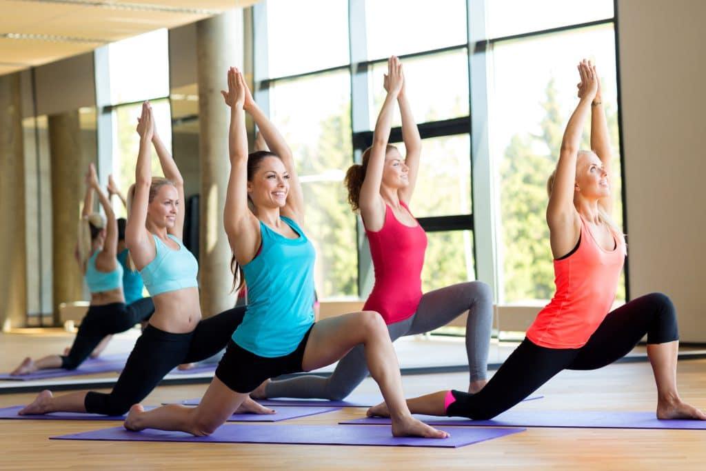 Quatros mulheres em uma sala praticando yoga.