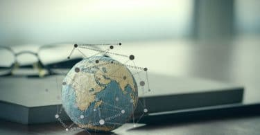 Pequeno globo terrestre, com desenhos de mapas pontilhados em cima dele, em cima de uma mesa de madeira com um óculos e um caderno ao fundo.