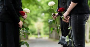 Pessoas vestidas de preto, em um cemitério, segurando rosas vermelhas e brancas.