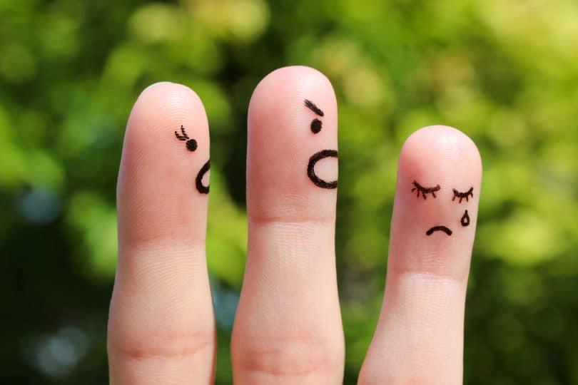 """Desenho de pessoinhas em dedos das mãos,. Duas das """"pessoas"""" estão brigando com a terceira, que está chorando."""