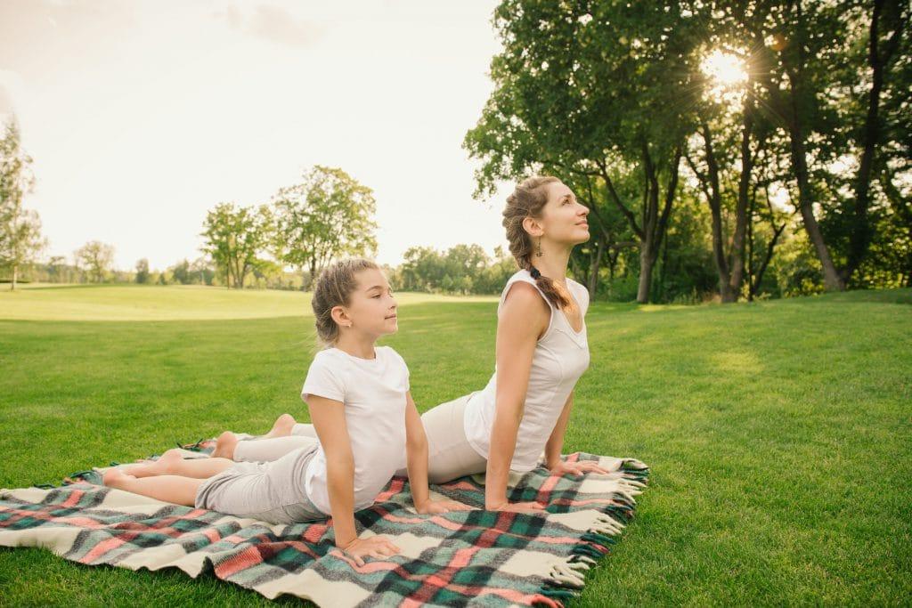 Mãe e filha fazendo yoga em um parque aberto.
