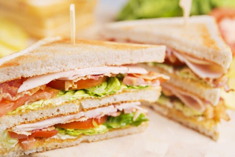 Duas metades de sanduíche, em cima de uma mesa.