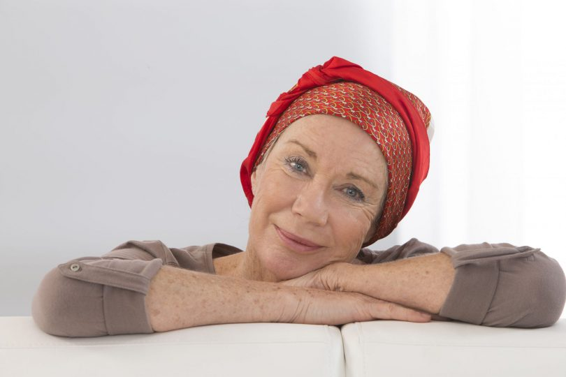 Mulher debruçada em seus dois braços. Ela está vestindo uma camisa de manga longa marrom e em sua cabeça usa um lenço vermelho.