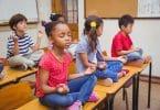 Crianças em posição de meditação em cima de suas mesas escolares.