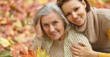 Mãe idosa e filha abraçadas, sorrindo, com folhas de outono ao fundo.