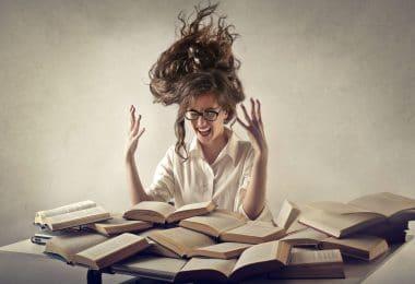 Mulher vestida de branco, com os cabelos em pé, gritando com as mãos pra cima, cercada de livros abertos .