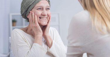 Mulher com as duas mãos sobre o rosto. Ela está sorrindo e usa um pano em sua cabeça cobrindo o cabelo raspado devido ao tratamento do câncer. Ela é branca, tem os olhos azuis e está vestindo uma camisa de mangas longas bege.