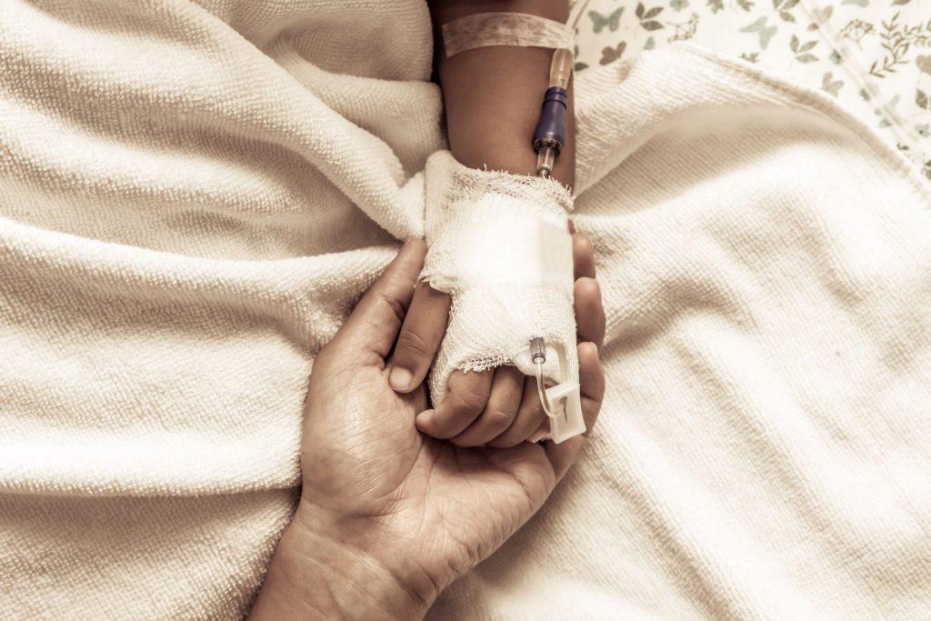 A imagem foca na mão de um homem adulto segurando a mão de uma criança que está tomando soro.