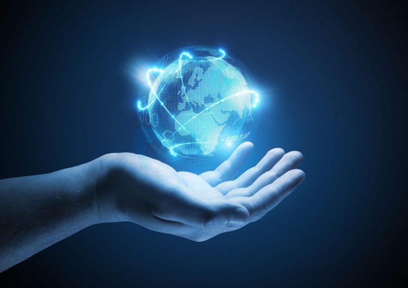 Mão humana segurando uma projeção do planeta terra azul iluminado.