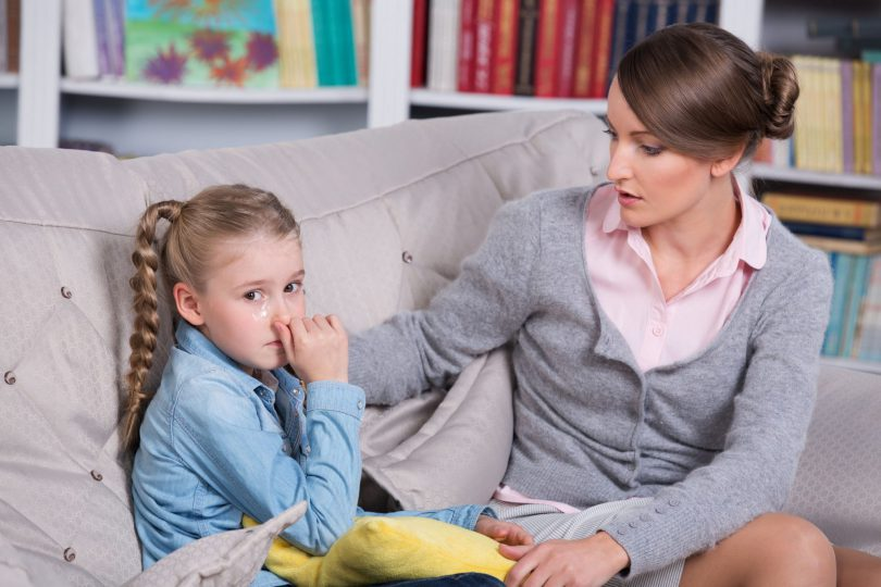 Criança menina sentada em um sofá, triste com a mão na boca enquanto a sua mãe olha pra ela e coloca a mão no seu ombro.