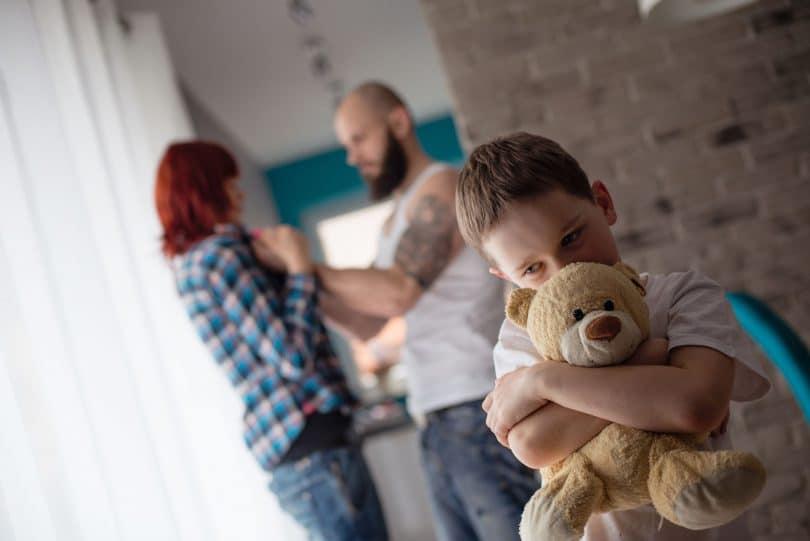 Criança branca triste, assustada, com os pais brigando ao fundo.