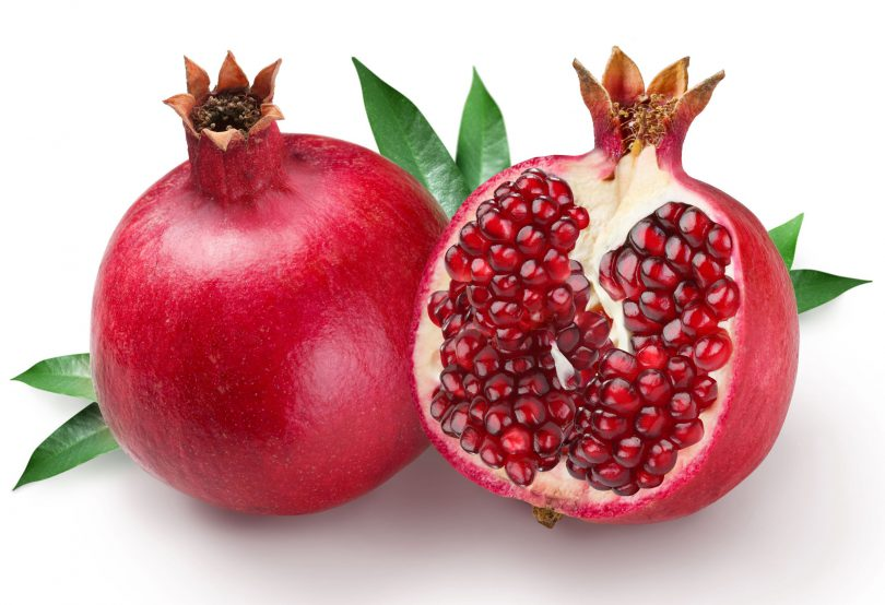 Duas frutas romãs em cima de uma mesa branca, uma fechada e outra cortada ao meio.