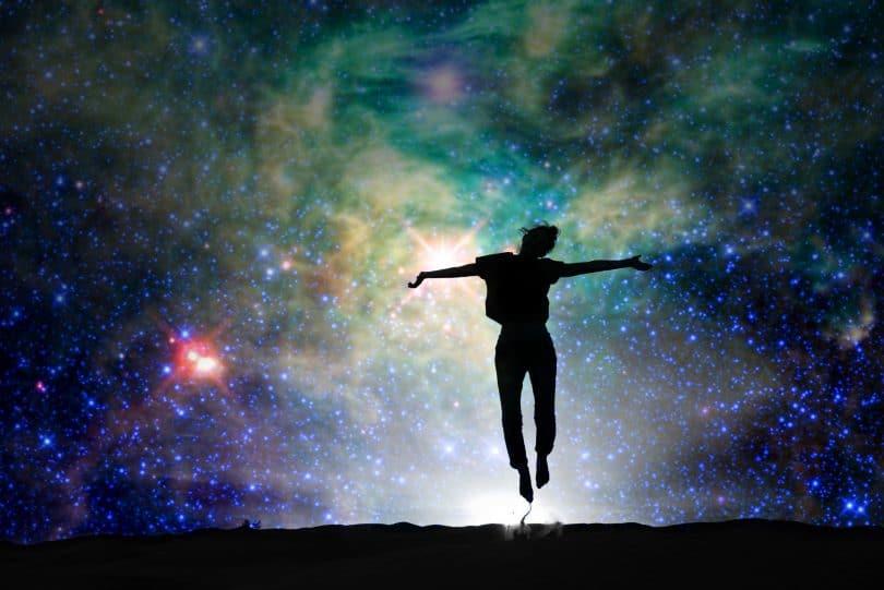 Silhueta de pessoa pulando na grama com um céu colorido cheio de constelações ao fundo.