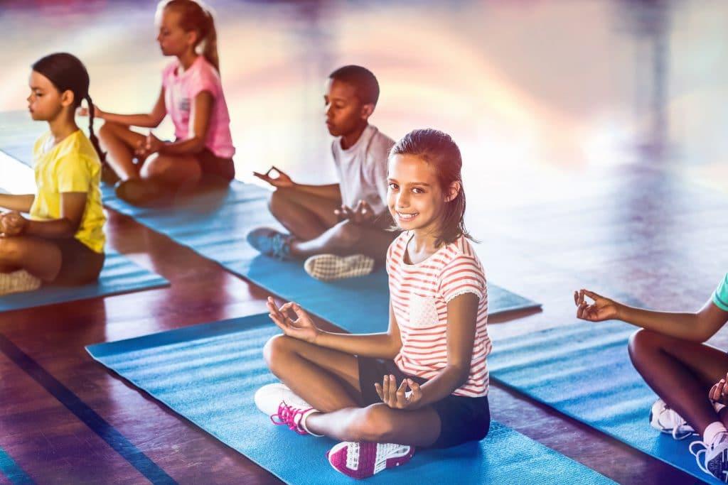 Crianças sentadas em tapetinhos de yoga azuis claro e em posição de meditação.