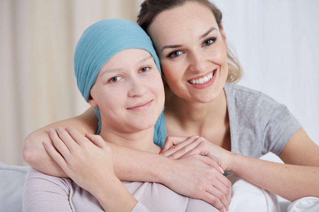 Duas mulheres abraçadas. Elas estão sorrindo. Uma tem cabelos loiros presos para trás e a outra usa um pano azul para cobrir a sua cabeça que está sem cabelos.