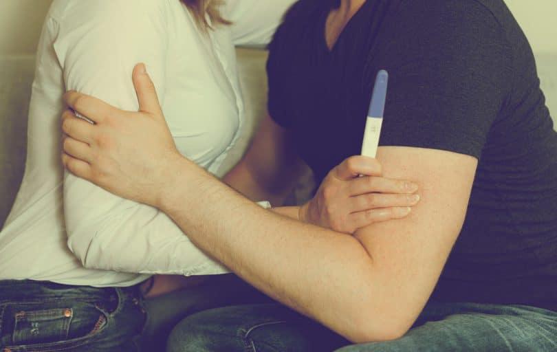 Homem e mulher se abraçando, sentados, sem mostrar as cabeças, enquanto mulher segura um teste de gravidez.