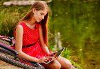 Menina vestida de vermelho, sentada no chão, em cima de uma bicicleta, enquanto mexe em um tablet, em um parque, com um lago ao fundo.