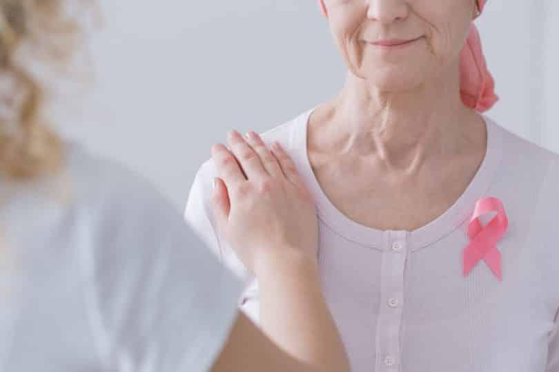 Mulher apoiando o braço sobre o ombro de uma mulher mais velha, com lenço na cabeça, que sofre de câncer de mama.