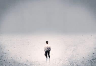 Homem vestido de branco parado no meio de uma sala grande e branca.