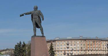 Estátua de homem baixinho, dando uma ordem com a mão, em cidade antiga.