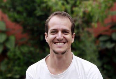 Homem sorrindo com um jardim ao fundo.