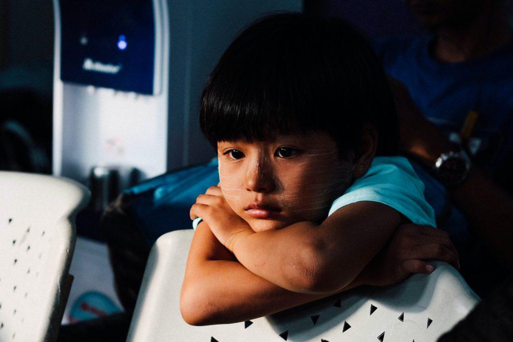 Criança apoiada em uma cadeira olhando para frente com tristeza