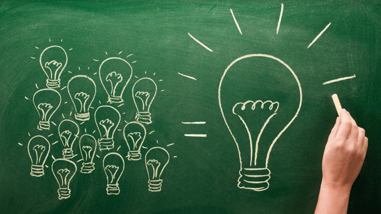 Mão desenhando em lousa com giz várias lampadas pequenas com um sinal de igual e uma lampada maior.