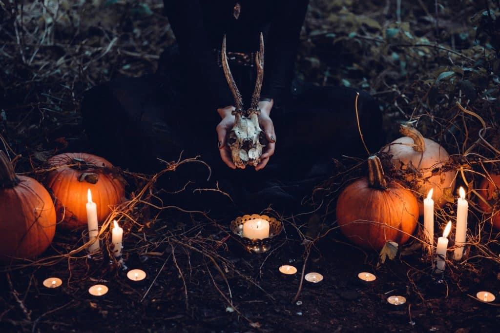 Mulher segurando o crânio de um animal enquanto senta no chão ao lado de velas e abóboras.