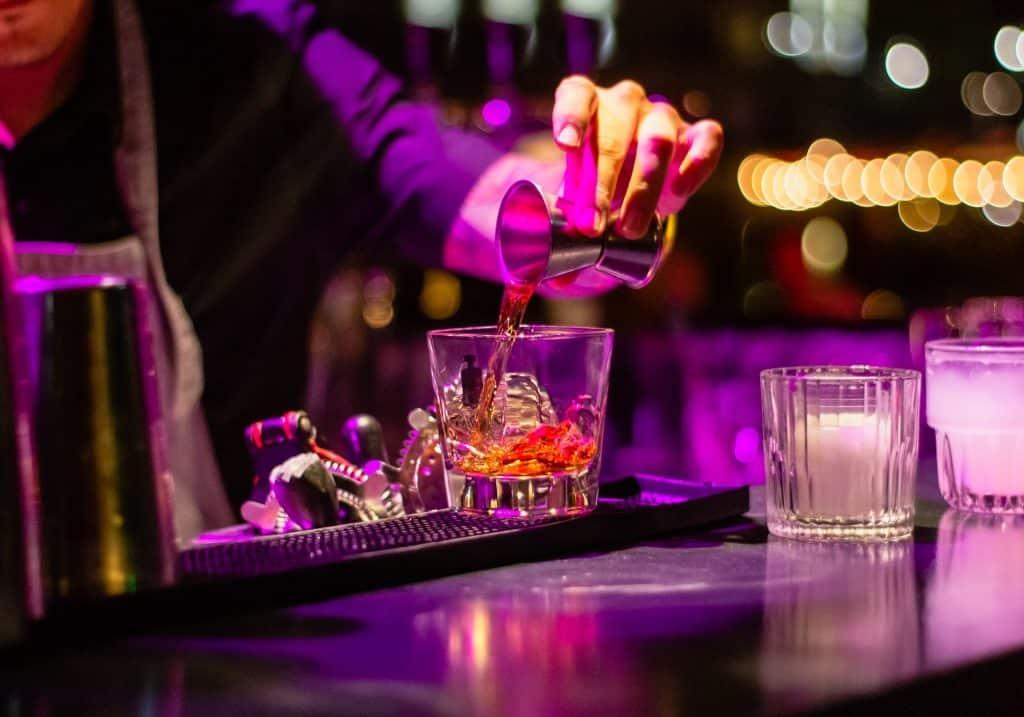 Bartender despejando em um copo uma dose de bebida alcoólica destilada.