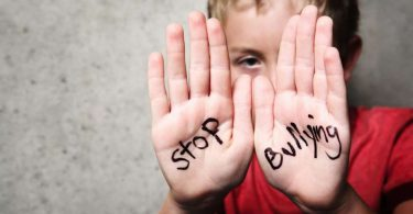 criança com as mãos abertas mostrando as palavras pare o bullying, em inglês.
