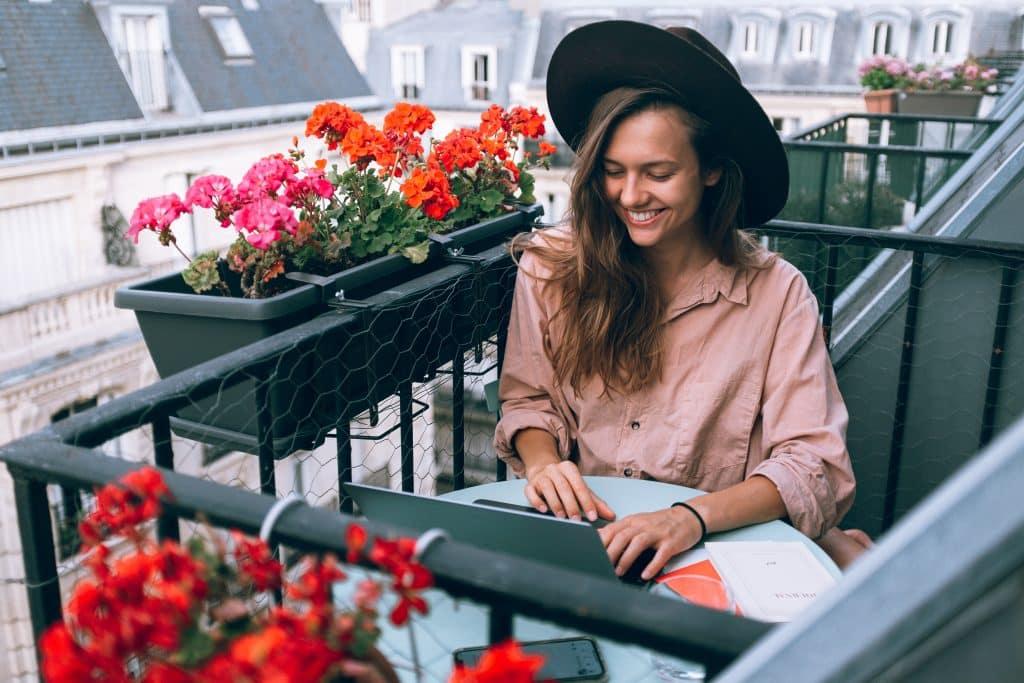 Mulher sentada em uma mesa da sacada ao lado de vasos de flores