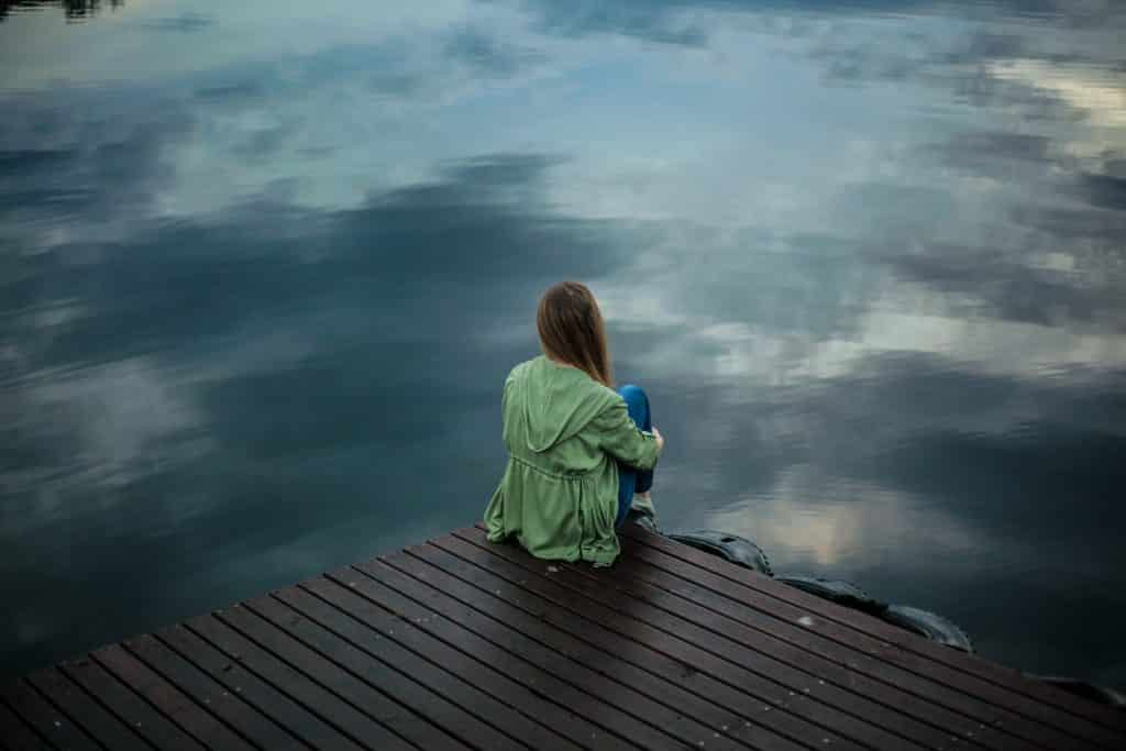 Mulher sentada em frente a um lago abraçando suas pernas