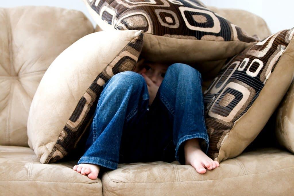 Criança sentada no sofá com almofadas ao redor