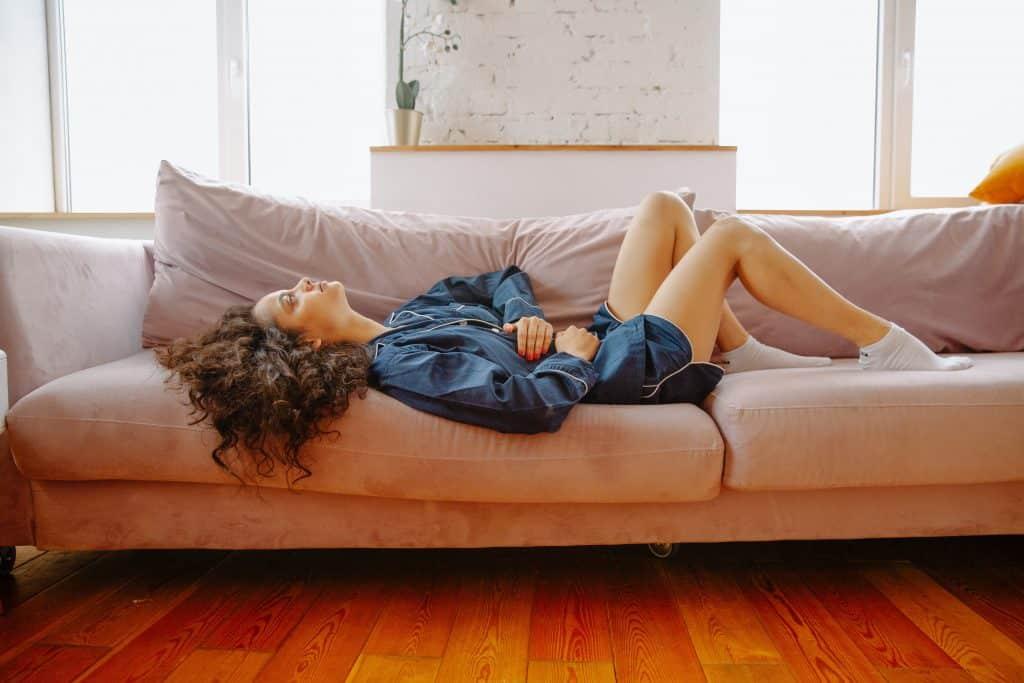 Mulher deitada no sofá com as mãos na barriga