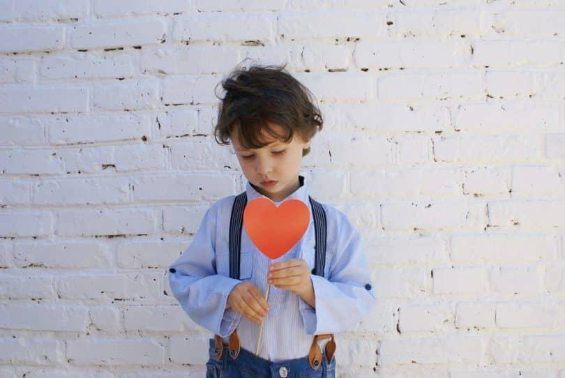 Criança segurando uma plaquinha de coração