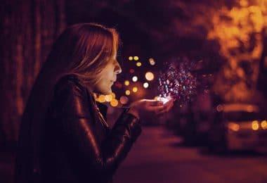 Mulher em uma rua, a noite, soprando das suas mãos glitters iluminados .