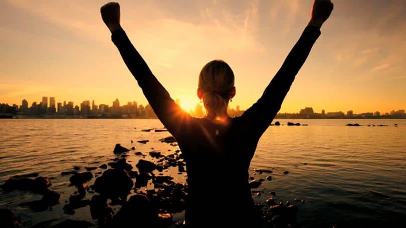 Silhueta de mulher em pé, com os braços para cima, observando o nascer do sol, em frente de um lago.