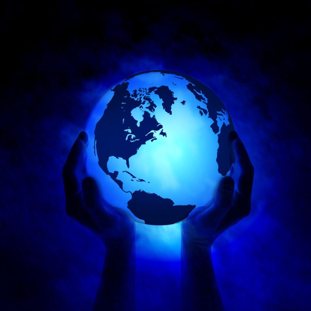 Duas mãos segurando um globo terrestre iluminado de azul.