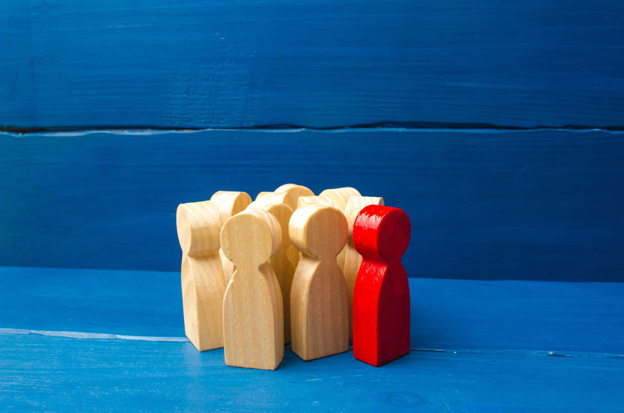Bonecos de madeira representando grupo social. Um boneco tingido de vermelho representa uma pessoa fora do grupo. Fundo azul.