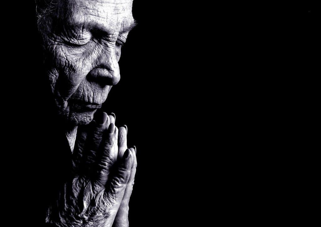 Mulher idosa rezando.